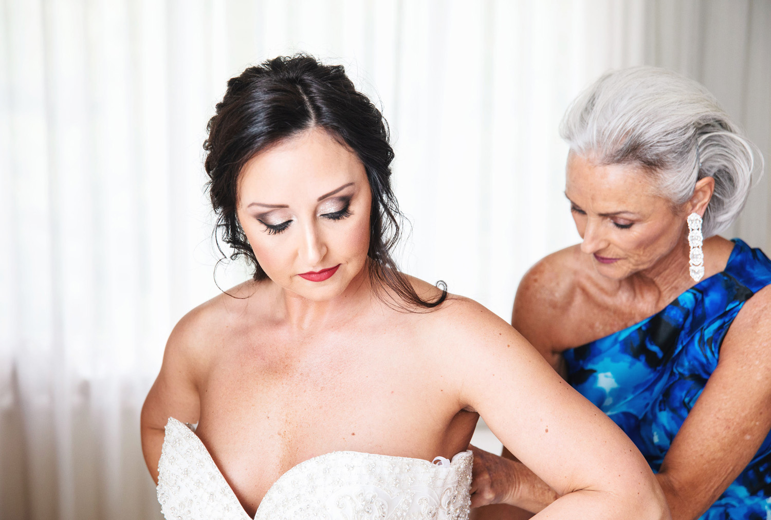 mother helping daughter into wedding dress by Monika Normand Photography